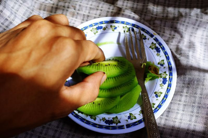 High angle view of man preparing food on bed at home
