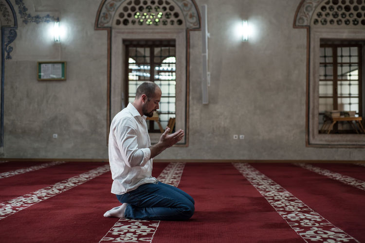 Side view full length of man praying while kneeling on carpet in mosque
