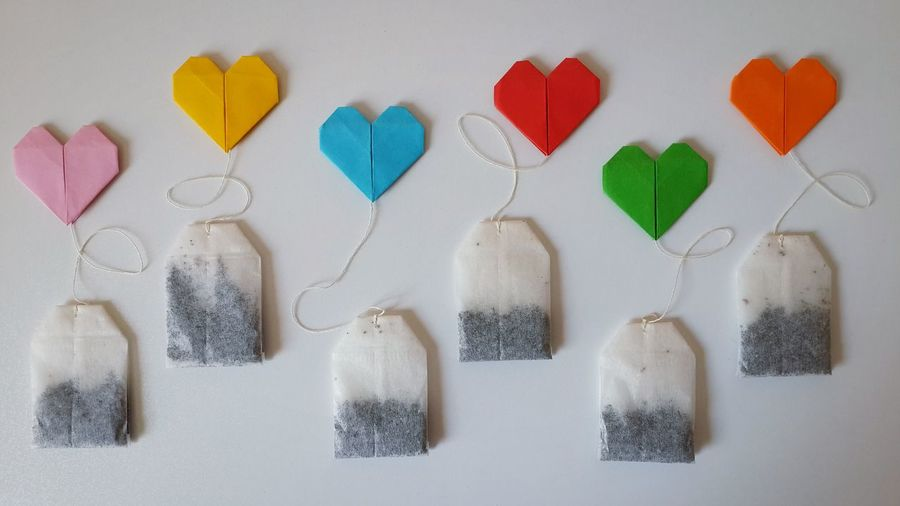 Directly above shot of teabags with colorful heart shape origami on white background