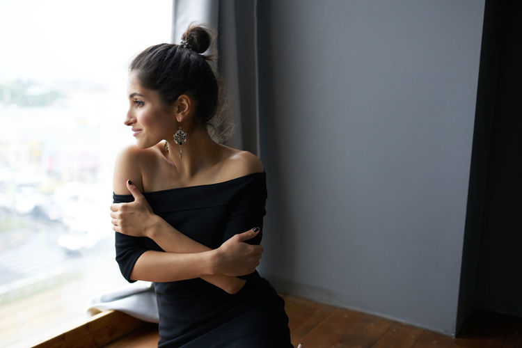 Woman looking away while standing against wall