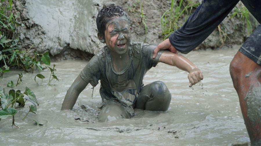 Siblings playing in muddy water