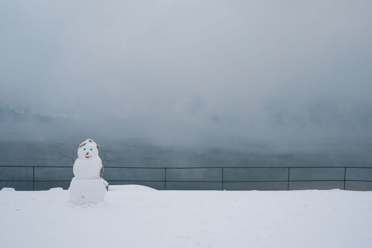 Snowman On Snow Covered Field By Railing During Foggy Weather