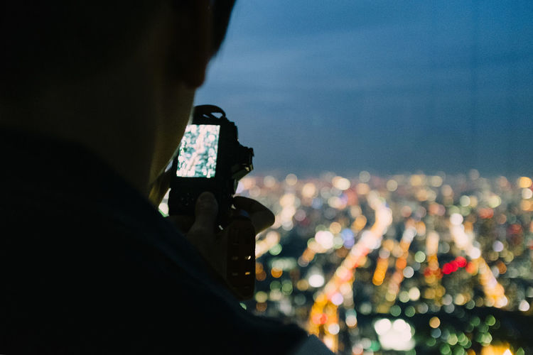 Rear view of person photographing illuminated cityscape against sky at dusk