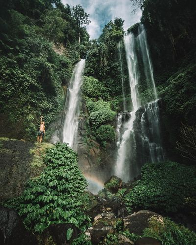 Low angle view of young man standing against waterfall in forest