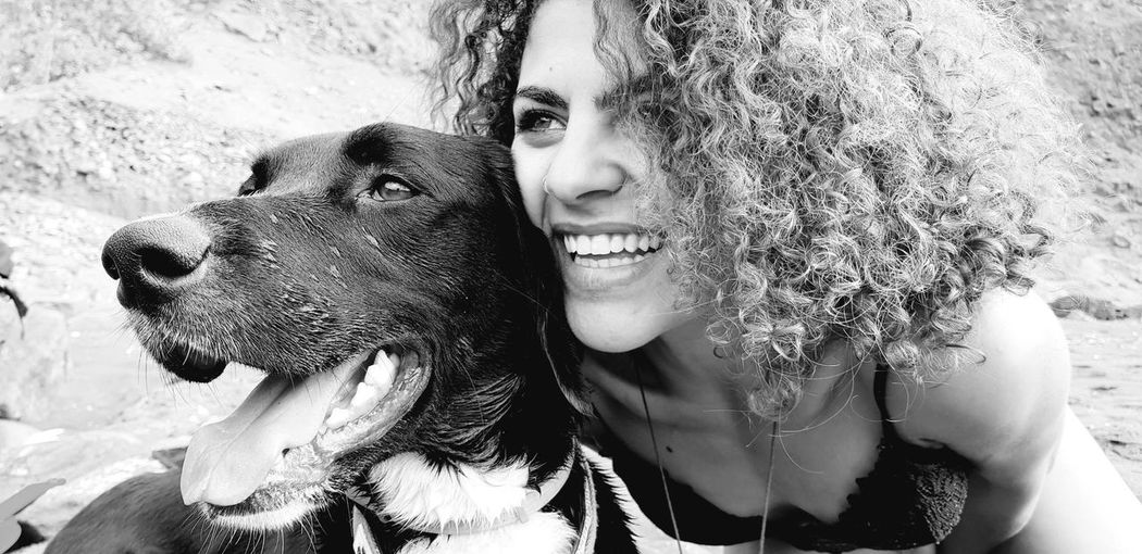 Close-up of cheerful young woman with dog at beach