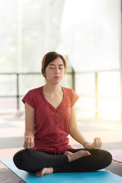 Balance Casual Clothing Cross-legged Exercising Eyes Closed  Front View Full Length Healthy Lifestyle Indoors  Leisure Activity Lifestyles Lotus Position Meditating One Person Practicing Real People Relaxation Relaxation Exercise Sitting Spirituality Wellbeing Yoga Young Adult Young Women Zen-like