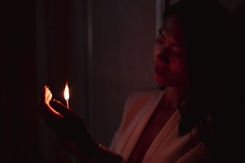 Close-up of woman holding lit candle in the dark