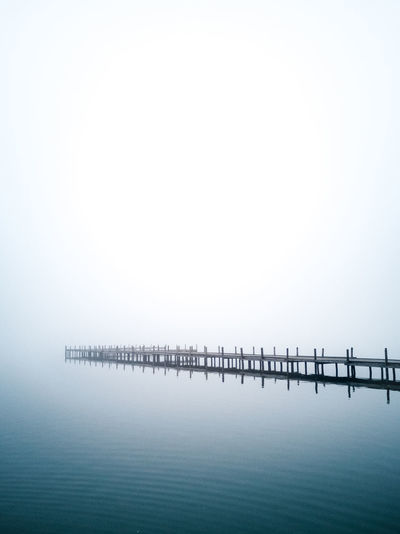Wooden pier over sea against clear sky