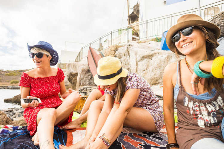 Happy friends sitting at beach