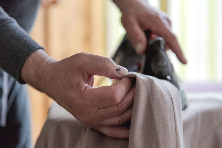 Cropped Image Of Man Ironing Clothes At Home