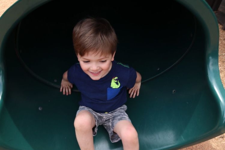 High Angle View Of Boy On Slide In Playground