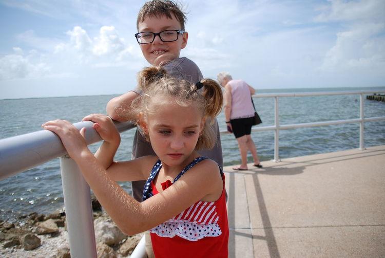 Siblings standing by railing at beach