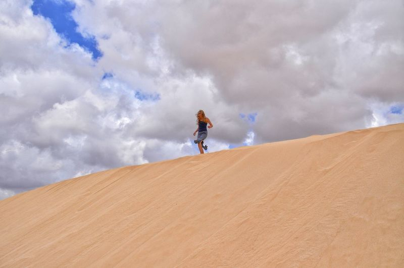 Low angle view of woman walking on sand dune against cloudy sky