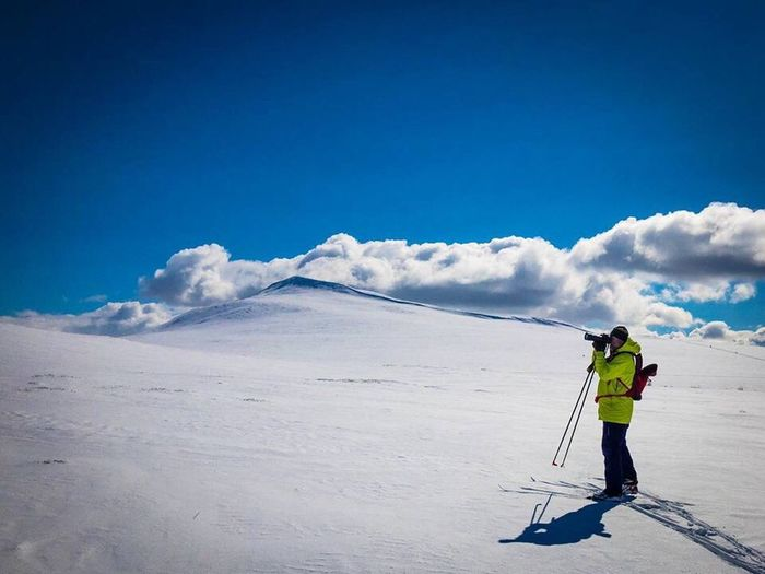 Man skiing on snow covered landscape against blue sky