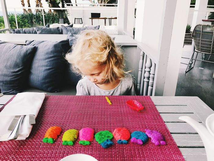 Cute Girl Playing With Colorful Clay On Table At Home