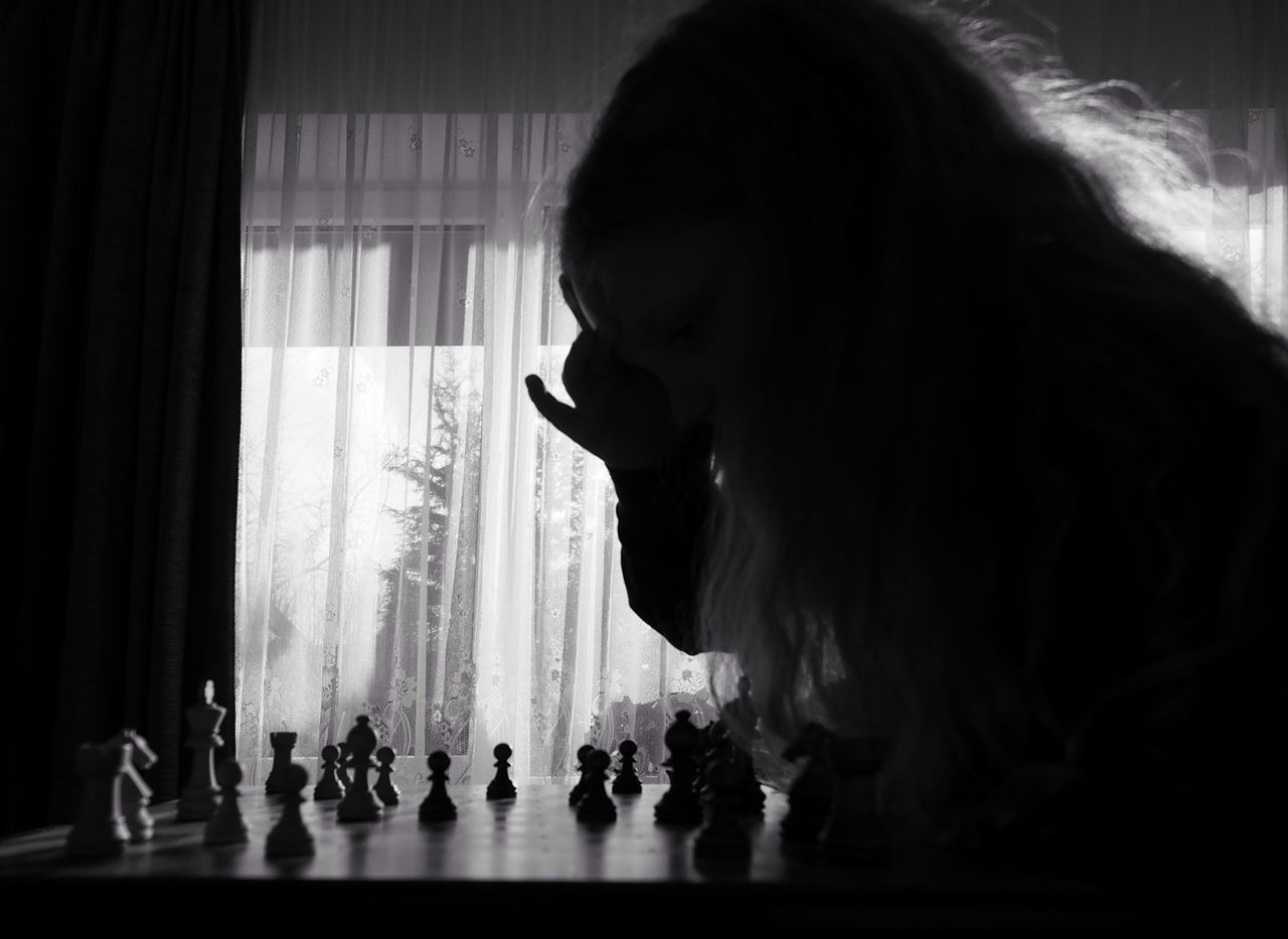 chess, real people, indoors, chess piece, playing, leisure games, leisure activity, one person, lifestyles, curtain, strategy, chess board, day, people