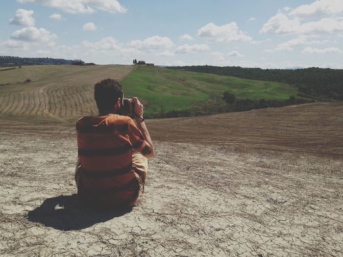 Rear View Of Man Photographing While Sitting On Dirt Field Against Sky