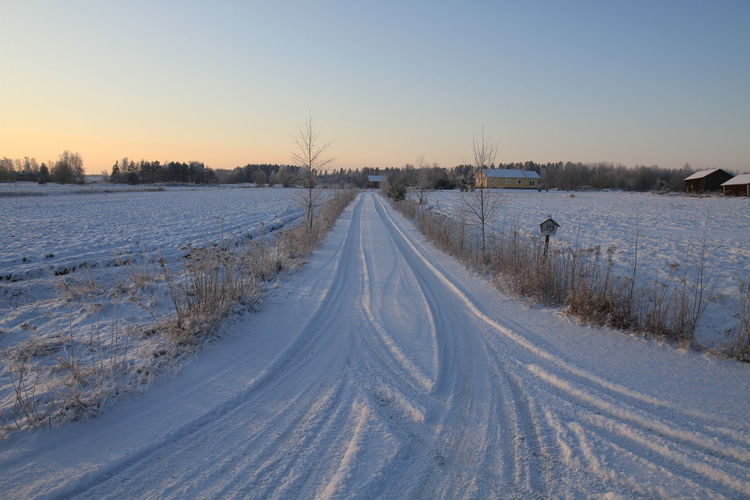 High angle view of tire tracks on snowcapped road during winter