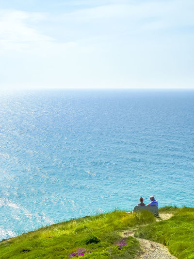 People Sitting On Bench At Cliff