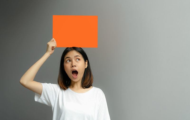 Young woman holding a blank poster for text on a white background. One Person Indoors  Front View Emotion Headshot Portrait Mouth Casual Clothing Studio Shot Gray Copy Space Standing Looking Up Mouth Open Gray Background Surprise Waist Up Looking Young Adult Hairstyle