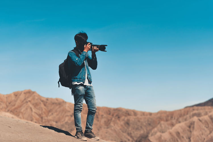 Man photographing at desert against sky
