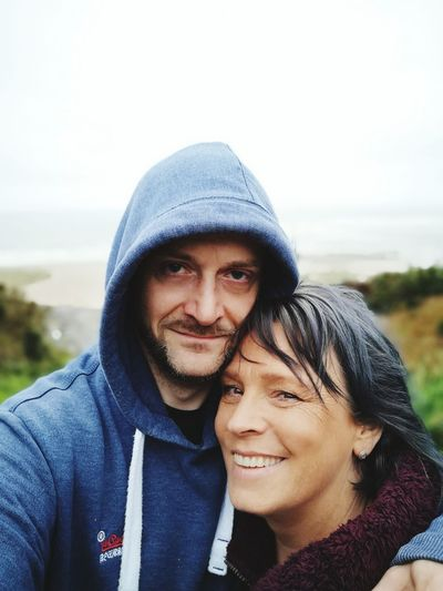 Portrait Of Smiling Man Embracing Woman