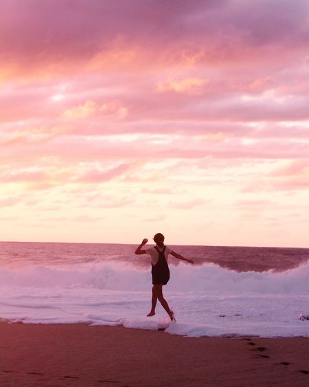 Rear view of girl jumping at beach against cloudy sky during sunset