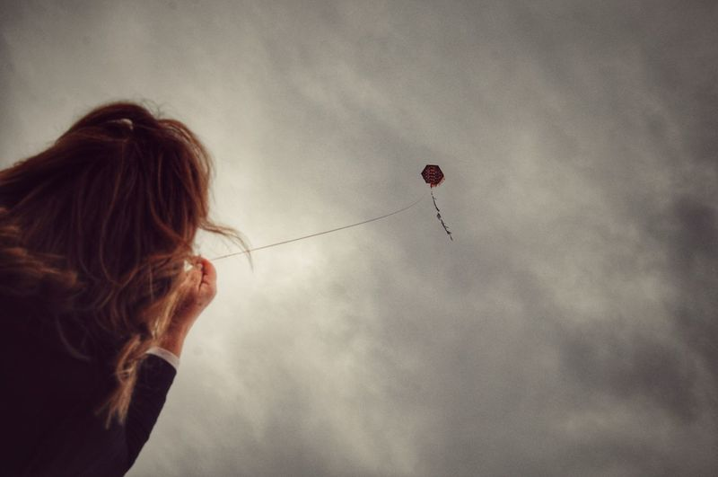 Low Angle View Of Woman Flying Kite Against Sky