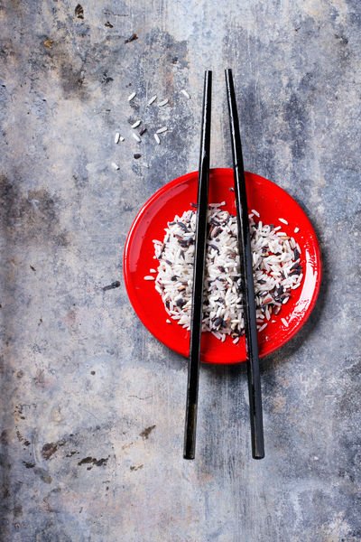 Uncooked black and white rice in red plate with black wooden chopsticks over tin surface. Top view. Asian  Assortment Black Rice Chopsticks Food Gray Background No People Red Red Plate Rice Uncooked White White Rice