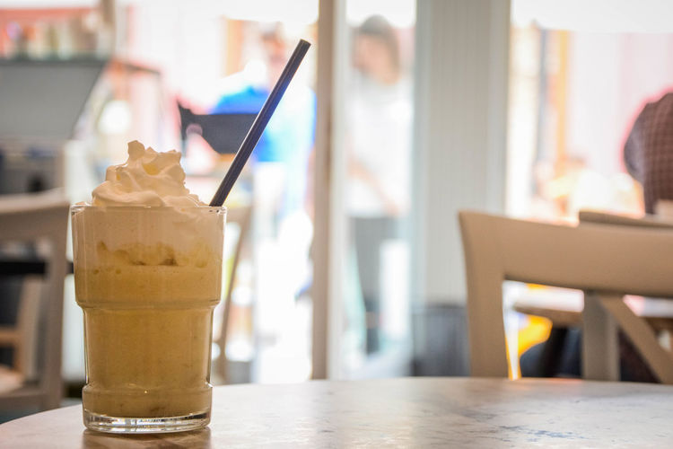 Close up view of banana shake in the glass. Banana Shake Cafe Close-up Dessert Drink Drinking Straw Focus On Foreground Food Food And Drink Freshness Glass Household Equipment Ice Cream Incidental People Indoors  Indulgence Refreshment Restaurant Straw Sweet Sweet Food Table Temptation