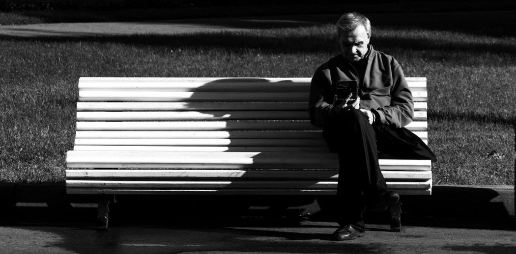 Senior man reading book while sitting on bench at park