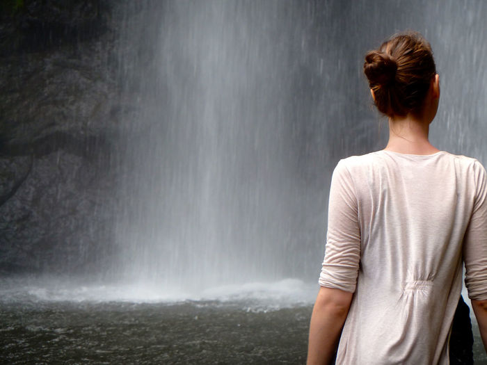 Rear view of woman standing in front of waterfall