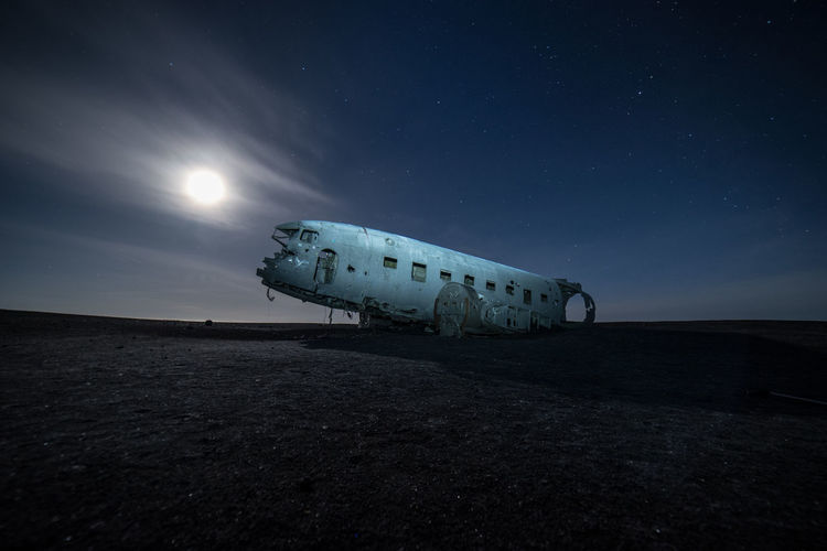 Abandoned Airplane At Beach Against Sky During Night