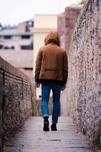 Rear view full length of man walking on footpath