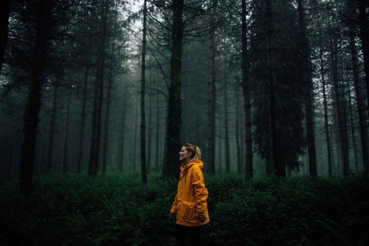 Girl standing by trees in forest
