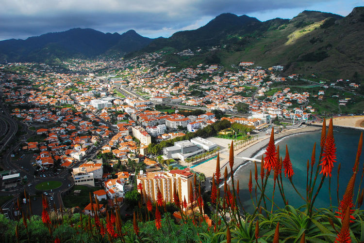 High angle view of townscape and mountains against sky, machico, madeira, portugal
