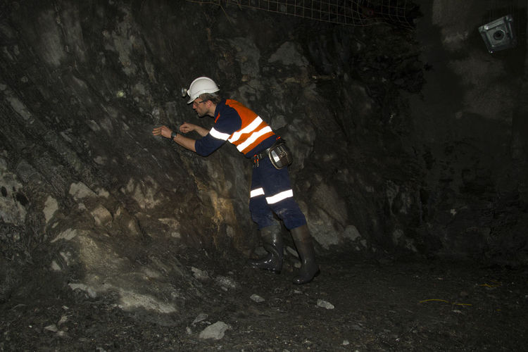 Geologist examining rock formation in cave