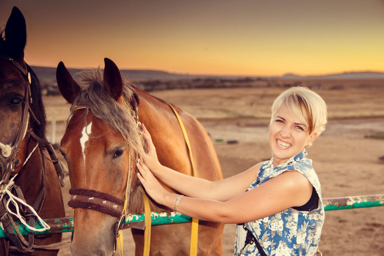 Portrait of smiling young woman holding brown horse on field