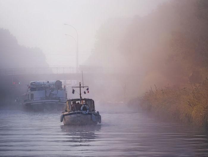 Boat in river against sky