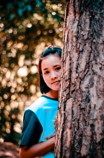 Portrait of teenage girl with tree trunk