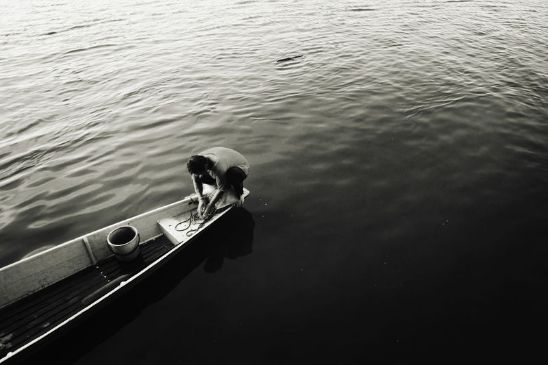 High angle view of man on boat moored in lake