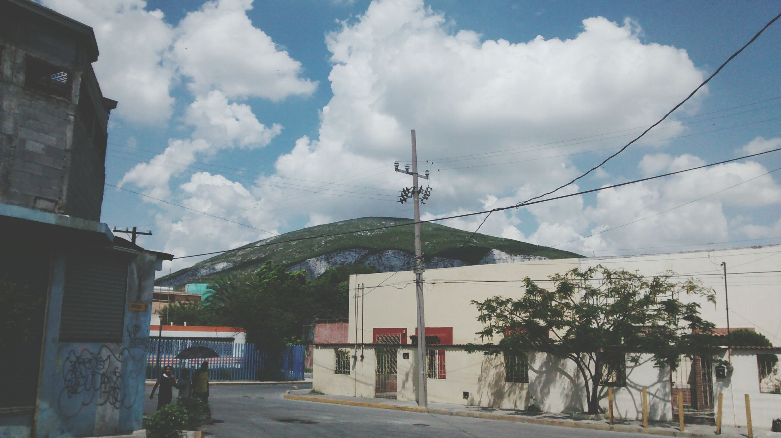 building exterior, architecture, built structure, sky, house, cloud - sky, power line, residential structure, cloud, residential building, town, mountain, tree, electricity pylon, cable, road, street, day, cloudy, outdoors
