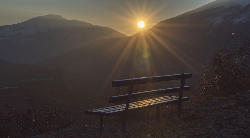 Empty bench on mountain against sky during sunset