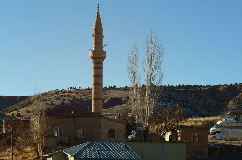 Minaret Architecture Branches And Sky Building Exterior Built Structure Clear Sky Hills Hillside View History Islam Minaret Mosque Niğde Place Of Worship Religion Roof Sky Speakers Tower Travel Destinations Tree Turkey Village Life Village View