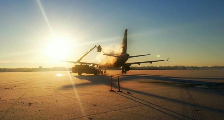 An Airbus A320 being deiced before it leaves for Phoenix, AZ From Milwaukee Wisconsin Clear Sky Sunlight