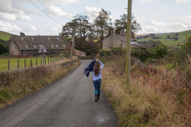 Rear view of man walking on road amidst field