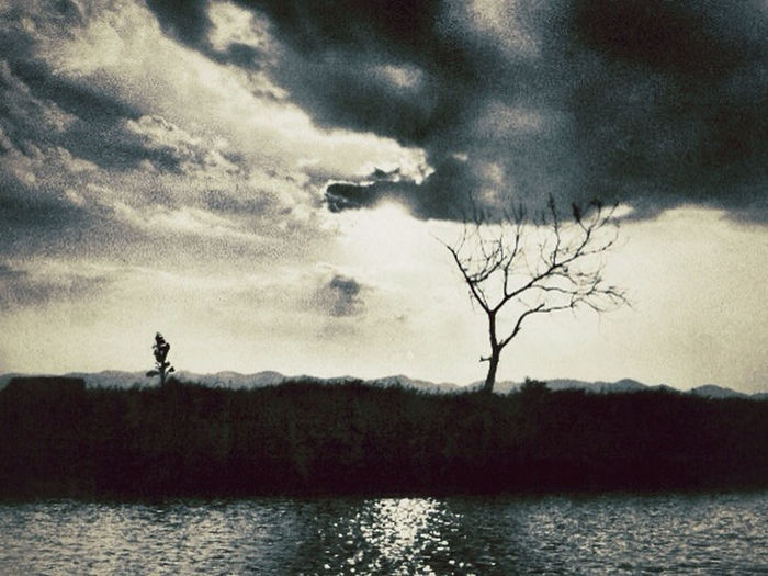 Silhouette of bare trees by lake against cloudy sky