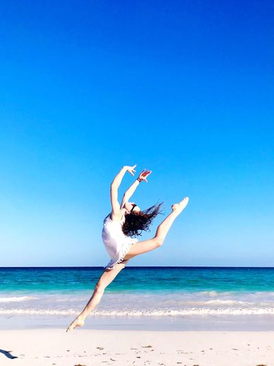 Joy Gymnastics Gymnast  Dancing Dancing On The Beach Playing On Beach Beach Long Hair Girl Jump For Joy Ring Leap Ring Jump Leap Leaping For Joy Sea Beach Copy Space Blue Clear Sky Full Length Horizon Over Water One Person Arms Raised Young Women Dancer Fun Young Adult Water Real People