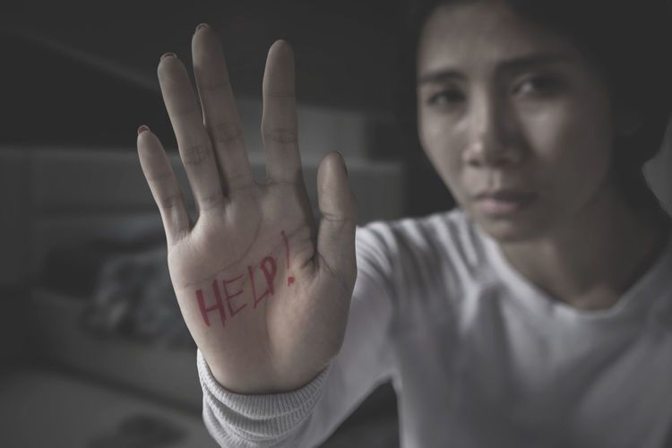 Portrait of victim showing help text on palm