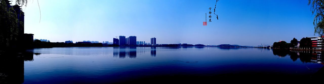 water, reflection, sky, architecture, waterfront, building exterior, built structure, outdoors, lake, nature, blue, day, tree, clear sky, no people, beauty in nature, city